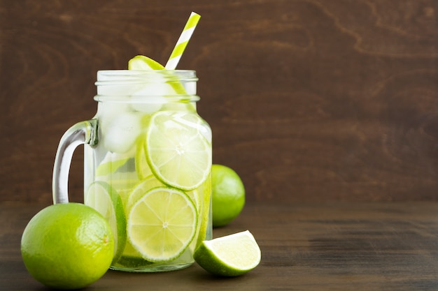 Mason jar glass of lemonade with lime and straw on wooden background-image
