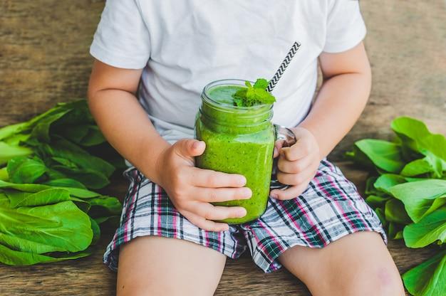 緑のほうれん草、バナナ、ココナッツミルクの健康スムージーをオートミールのスプーンで満たしたメイソンジャーマグ