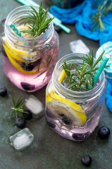 Mason jar mugs with homemade refreshing drink with blueberries and rosemary vegetarian food
