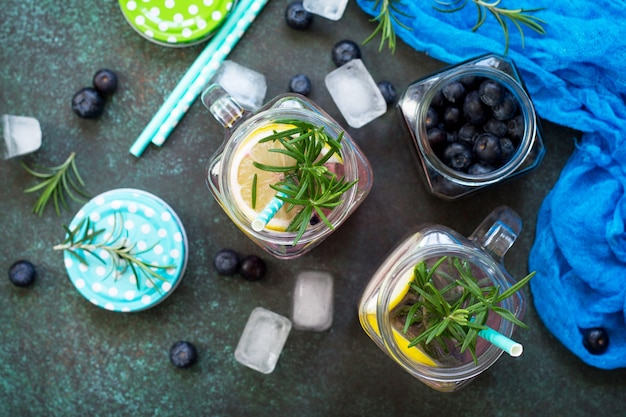 Mason jar mugs with homemade refreshing drink with blueberries and rosemary