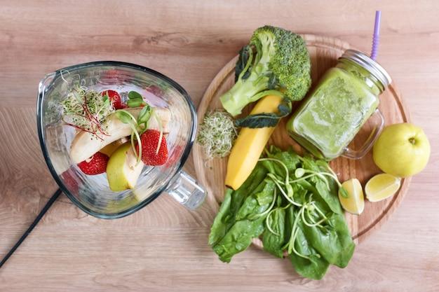 ブロッコリー、ほうれん草、マイクログリーン、ライム、バナナと木製の背景に材料でいっぱいのミキサーと食事療法の飲み物のメイソンジャー