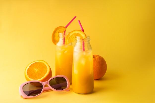 Мейсон банка свежего апельсинового сока на цветном фоне