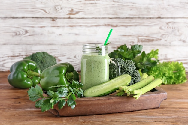 木製の表面に緑の野菜と健康的なスムージーのメイソンジャー