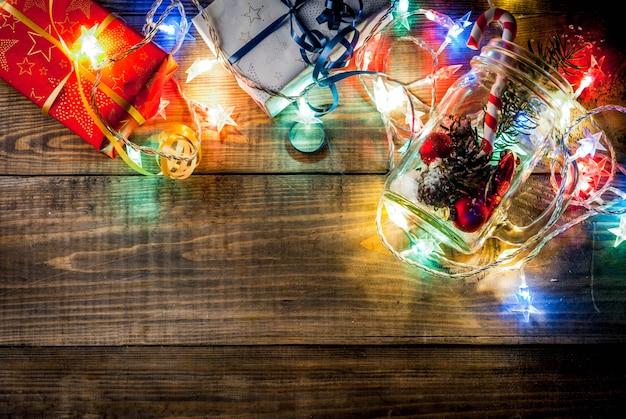 Кувшин мейсон с украшениями, еловые шишки, искусственный снег, конфета и еловые ветви. на деревянном фоне стола с зажженной гирляндой. копировать пробел сверху