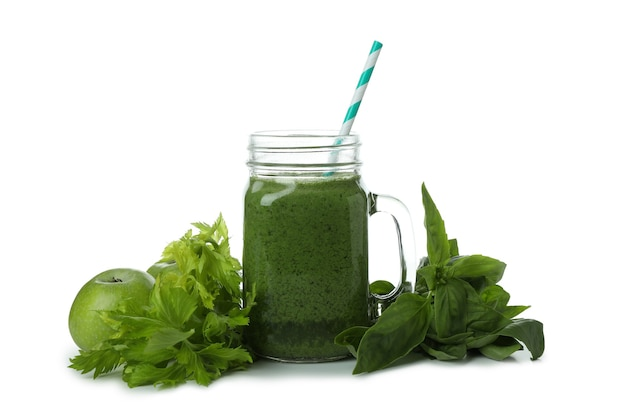 Mason jar with green smoothie and ingredients isolated on white background