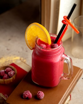 A mason jar with raspberry smoothie garnished with raspberry and orange slice