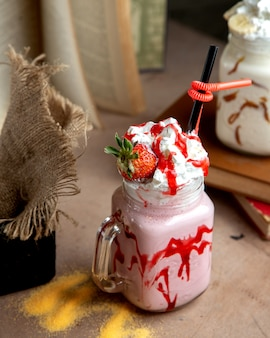 A mason jar with strawberry milkshake with strawberry syrup whipped cream and strawberry