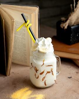A mason jar with vanilla milkshake and chocolate syrup whipped cream and banana