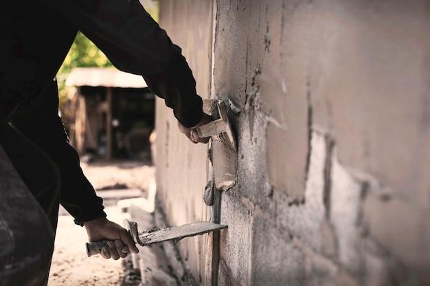벽을 만들기 위해 콘크리트를 미장하는 메이슨, 건설