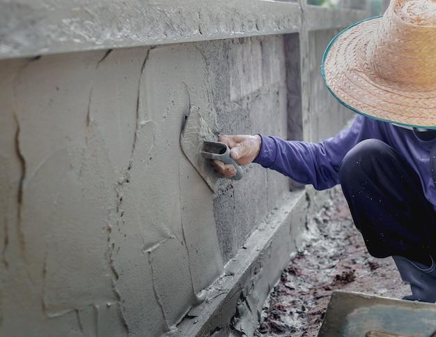 Mason 시골 태국 집 개념 품질을 개조하는 석고 도구를 사용하여 벽 배경 산업 작업자를 만들기 위해 콘크리트를 석고