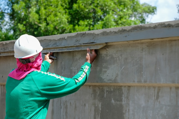 A mason worker plastering cement on concrete wall in hot weather at construction site.