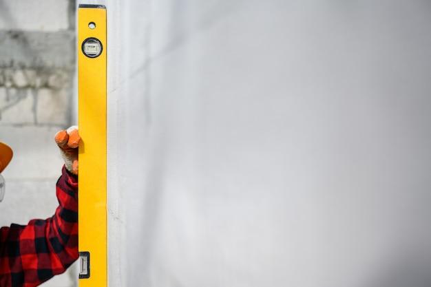 組積造の労働者は、水準器を使用して軽量のレンガの壁を調べ、壁が水準器と一致するかどうかを確認します。建設現場での基本的な軽量コンクリート組積造技術。