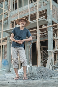 Masons wearing hats smiling as they stand holding shovels in house construction