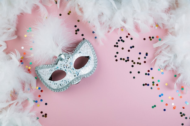 Masquerade carnival feather mask with colorful confetti and boa feather on pink background