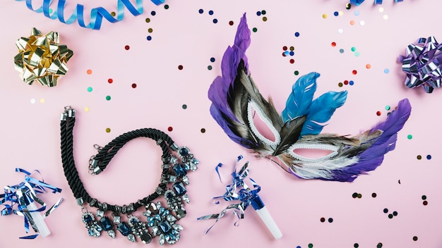 Masquerade carnival feather mask with confetti and necklace over pink backdrop