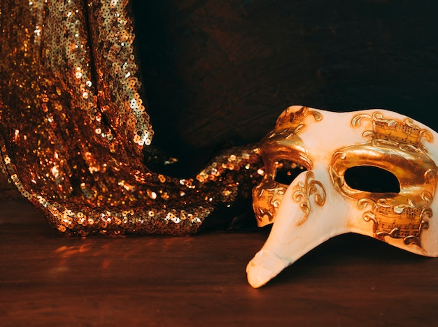 Masquerade mask and shiny golden sequins textile on wooden desk