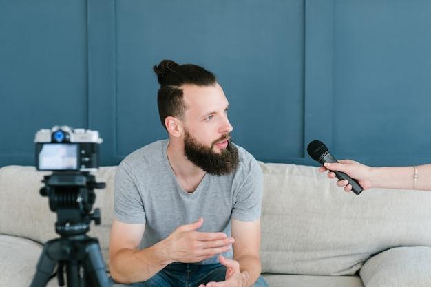 マスメディアの人気と有名なインフルエンサーのコンセプト。マイクを持っている女性ジャーナリストにインタビューをしている男性。