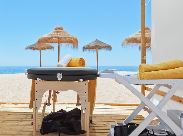 Massage area and a deck chair on the beach for therapy. near the sea.