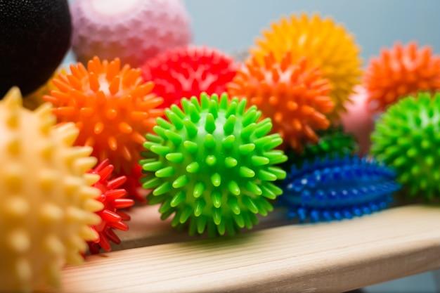 На полке лежат массажные шарики разных цветов.