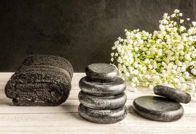 スパ用の玄武岩をマッサージし、タオルと白い花が暗いテーブルを残します。