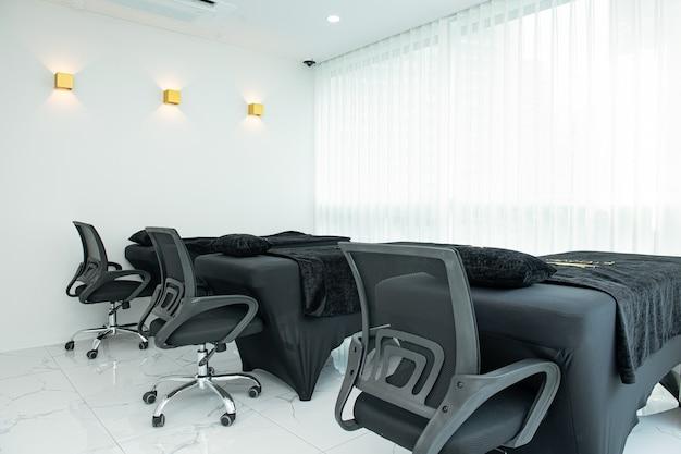흰색 바탕에 마사지 침대와 의자