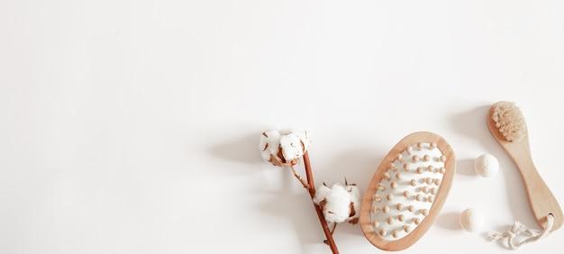 Массажная щетка, бомбы для ванны и хлопковая веточка плоской формы. концепция здоровья и гигиены.