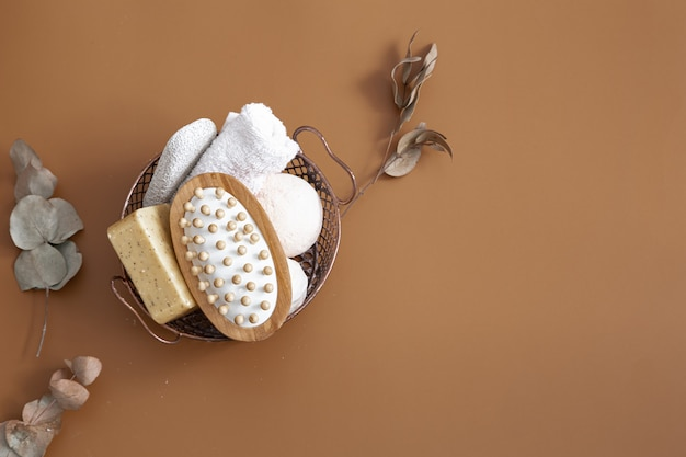 Массажная щетка, бомбы для ванны, мыло и полотенце в корзине на коричневом фоне вид сверху.