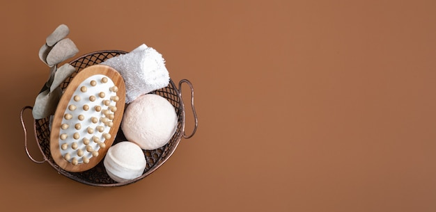 Massage brush, bath bombs and towel in basket on colored background top view.