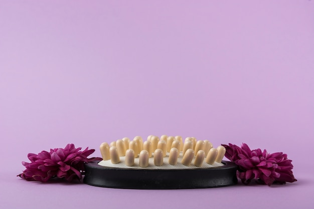 Massage brush with pink flowers against purple background