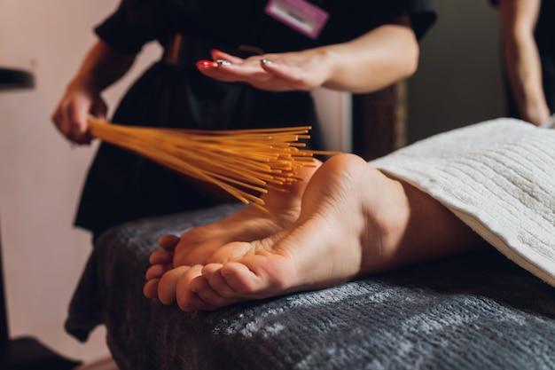 Massage of female feet with bamboo sticks