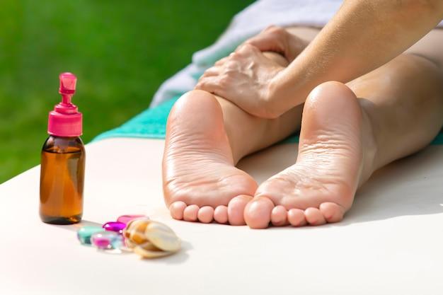 다리 마사지, 오일이 있는 여성 발, 야외 돌. 안마사, 마사지사의 여성 발과 치료사의 손의 사진을 닫습니다. 전문 물리치료사. 알아볼 수 없는 사람이 거짓말을 하고 휴식을 취하고 있습니다.