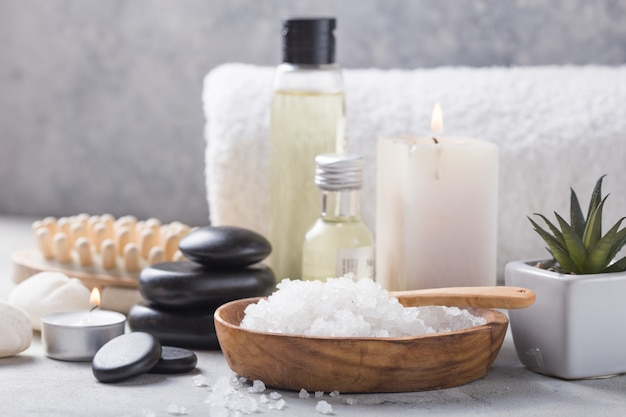 Massage oil bottle of aroma essential and natural fragrance salt with stones, candles on concrete grey table.