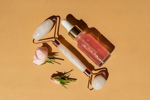ピンクの自然腎炎の顔に美容液またはローズエッセンシャルオイルでクォーツローラーをマッサージします