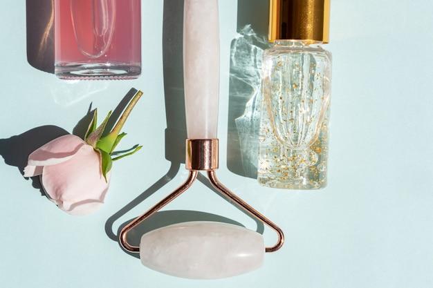 Ролик для массажа лица из розового кварца с флаконами косметического масла или сыворотки на синем фоне. концепция ухода за кожей в домашних условиях. сыворотка с золотом 24k и розовая вода для ухода за лицом.