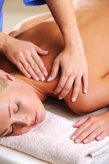 Massaggio per la spalla per la giovane donna nel salone di bellezza