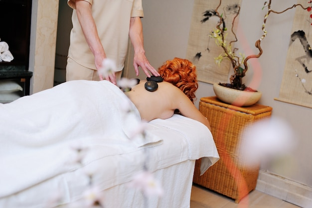 The massage stones on the body of a red-haired young girl. stone therapy