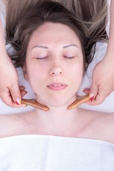 Помассируйте шею девушки натуральным деревянным массажером, крупным планом. уход за лицом и шеей. лимфодренажный массаж лица деревянным массажером