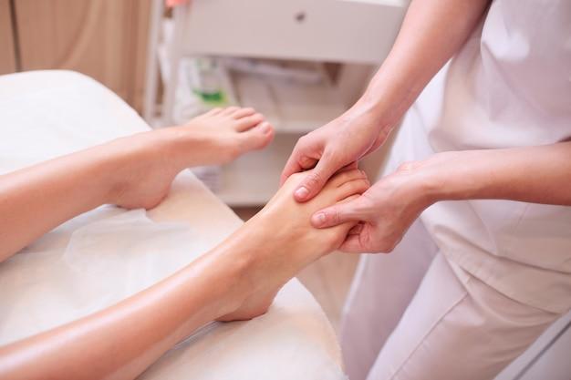 マッサージセラピストはかなり若い女の子に足のマッサージをします