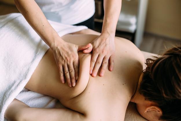 スパで女性の身体をマッサージするマッサージセラピスト
