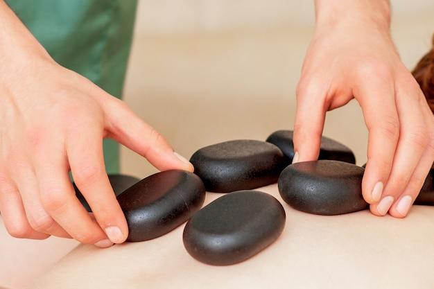 마사지 치료사 손이 인간의 등에 뜨거운 마사지 돌을 올려 놓고 닫습니다.