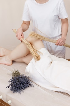 The massage therapist makes foot massage with special brooms on the couch. self-care