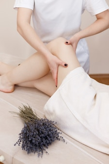 The massage therapist massages the woman's legs, lavender lies next to her. taking care of yourself. aromatherapy