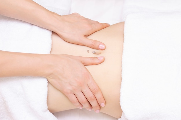 Massage therapist massaging a woman stomach. massage and body care. spa body massage woman hands treatment.