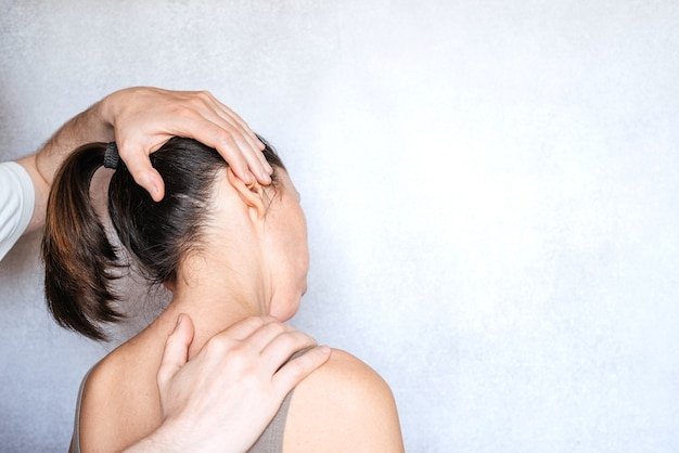 여성의 목을 조작하고 목 통증을 완화하기 위해 척추 조정을 시행하는 마사지 치료사