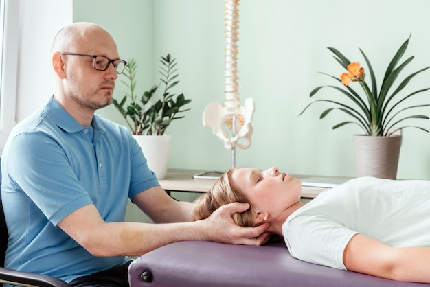 Массажист, проводящий черепно-крестцовую терапию пациенту женского пола, нежными прикосновениями манипулирует суставами черепа или черепа.