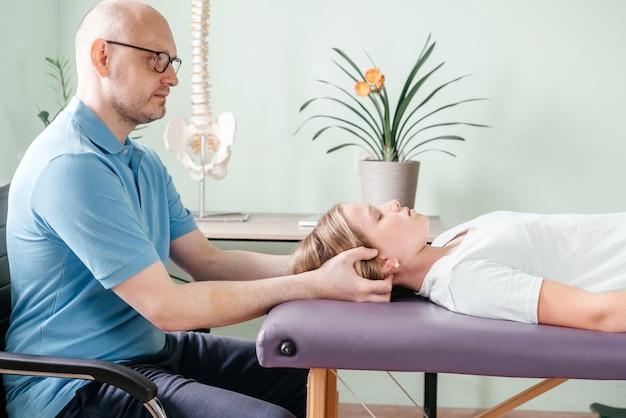 여자 아이 환자에게 두개골 천골 요법을 수행하고 두개골이나 두개골의 관절을 조작하기 위해 부드러운 터치를 사용하는 마사지 치료사