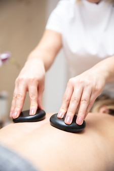 Massage therapist using hot lava stones during health spa relaxing stone therapy