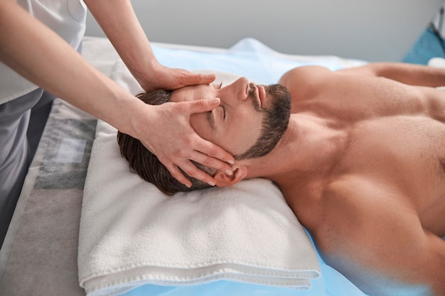 Massage therapist works with head of male lient lying on couch in contemporary clinic
