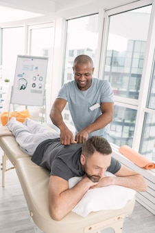 Massage therapy. pleasant cheerful man having a massage while visiting a rehabilitation center