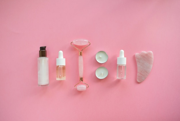 ピンクの天然翡翠で顔をクォーツローラーでマッサージします。美容美容液入りのガッシュマッサージツール。アンチエイジングと自宅でのリフティング。フェイシャルケアマッサージとリラクゼーションのコンセプト。